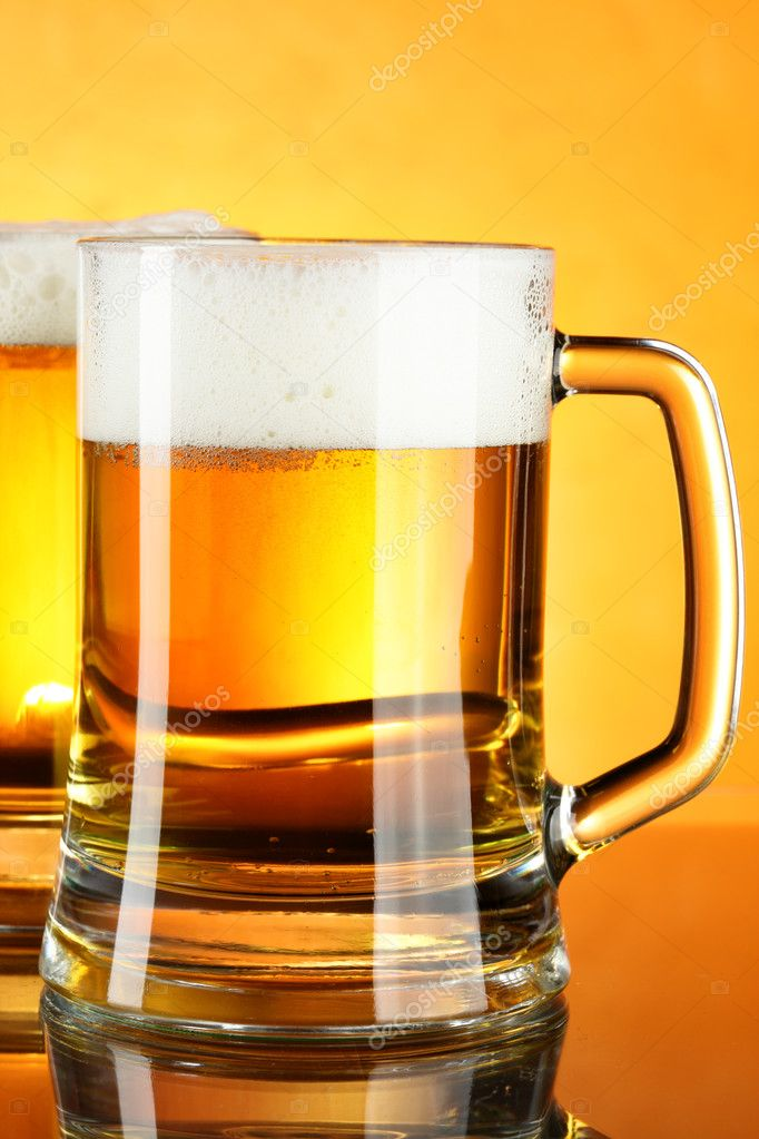 Beer mugs with froth over yellow background — Stock Photo #1417197