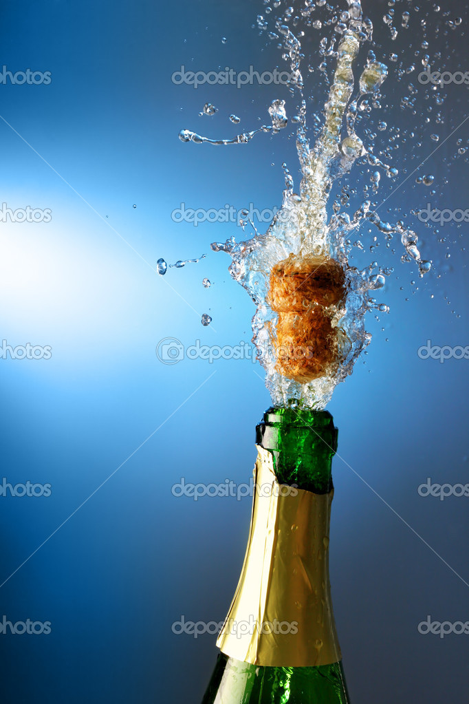 Bottle of champagne with splashes over blue background — Stock Photo #1427153
