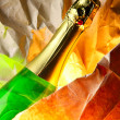 Bottle of champagne and warping paper — Stock Photo