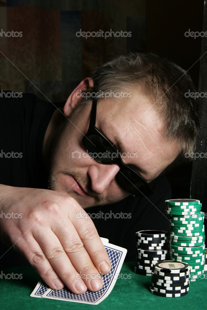 Poker gambler with sun glasses close-up. Focus on the hand and chips. — Stock Photo #1435151
