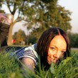 Young happy woman lying on the grass - Stock Photo