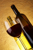 Copa de vino tinto y botellas — Foto de Stock