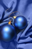 Christmas balls over blue silk — Stock Photo