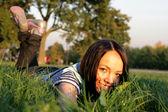 Young happy woman lying on the grass — Stock Photo