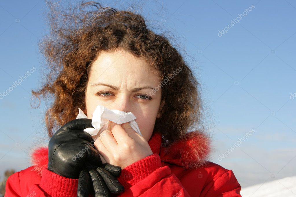 Young woman blowing her nose at tissue — Stock Photo #1440556