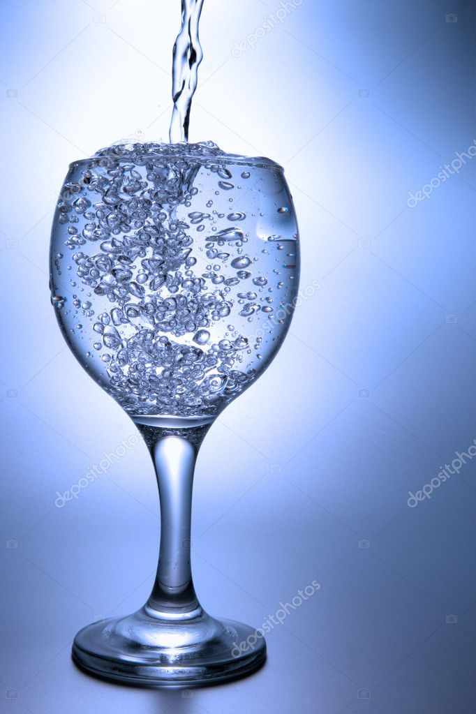 Clear liquid pour into footed glass over blue background — Stock Photo #1440813