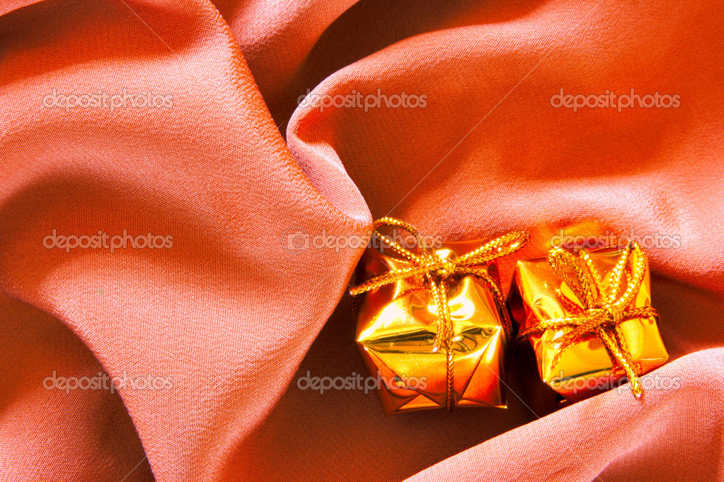 Expensive gifts over silk background with folds — Stock Photo #1441120