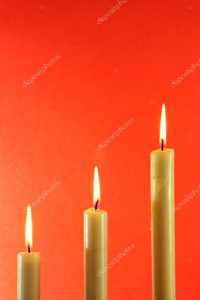 Three burning candles over light red background — Zdjęcie stockowe #1441508