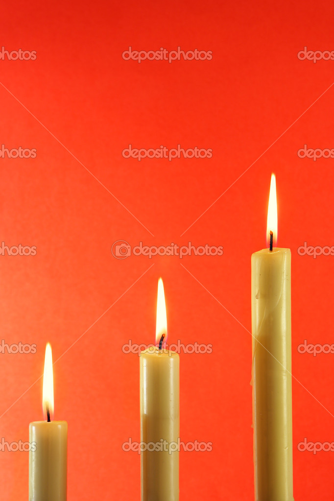 Three burning candles over light red background — Lizenzfreies Foto #1441508