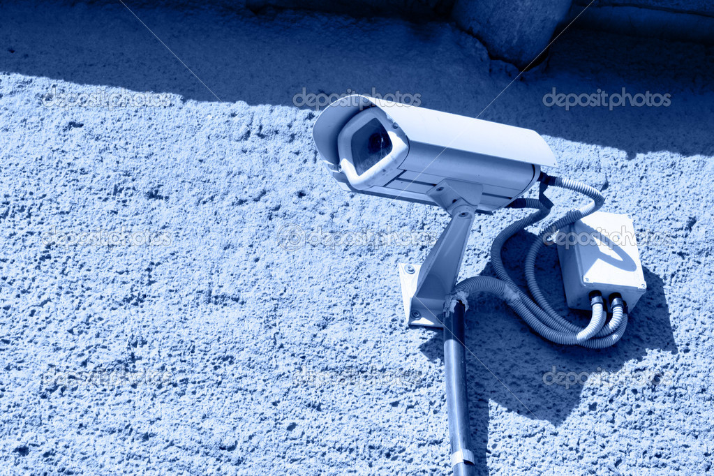 Security camera mounted on stone wall toned in blue — Stock Photo #1441575