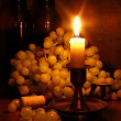 Grapes and candle - Stock Photo