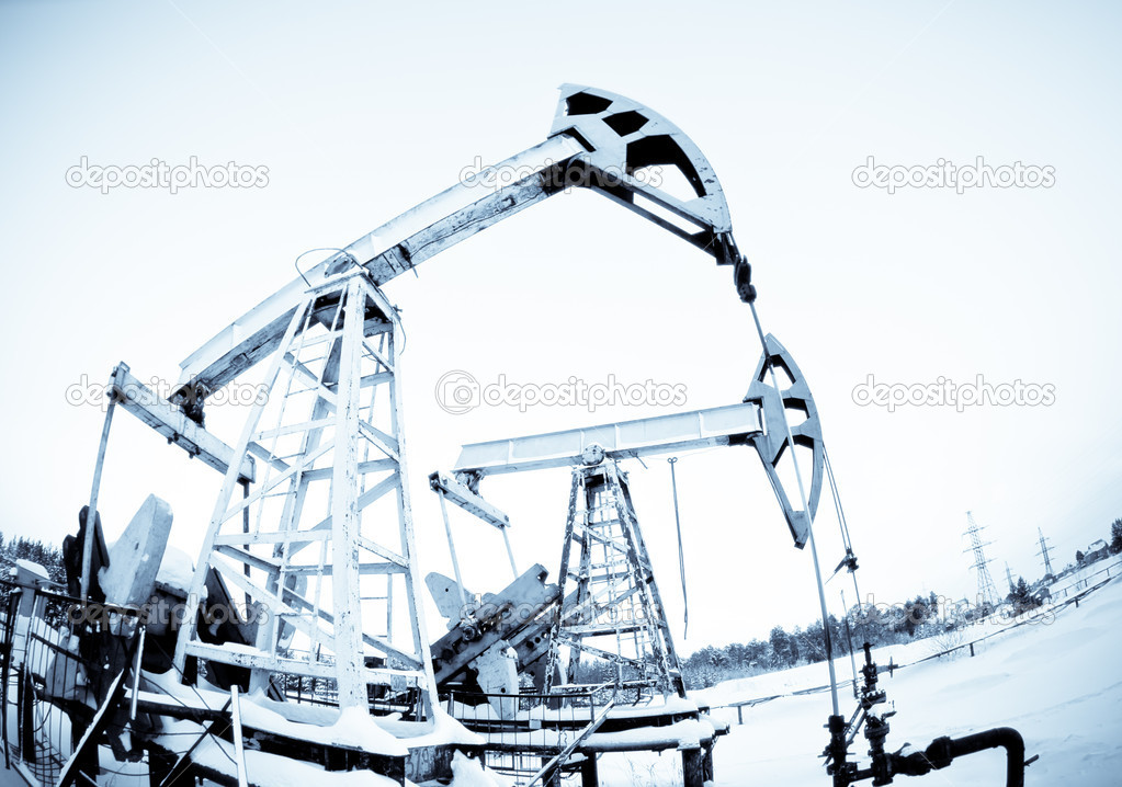 Two oil pump on the field, frosty winter day. selenium tone. — Stock Photo #1891701