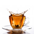 Glass cup of tea withsplash out — Stock Photo