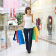 Casual woman walking with shopping bags - Stockfoto
