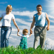 Family under blue sky - Stock Photo