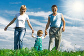 Family under blue sky — Stock Photo