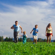 Stock Photo: Family mother father and two child run o