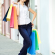 Stock Photo: Young woman with multi-coloured bags