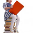 Schoolgirl sitting on the heap of books — Stock Photo