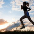 Silhouette woman run under blue sky - Stock Photo