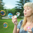 Young girl makes soap bubble — Stok fotoğraf