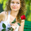Young beauty woman in park with flower — Stock Photo
