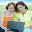 Stock Photo: Two beautiful girls with laptop computer
