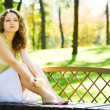 Young beauty woman sit on bench — Stock Photo