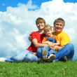 Happy family sit on green grass under sk - Stockfoto