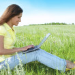 Pretty woman with laptop on the green gr — Stock Photo