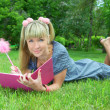 Foto Stock: Young blonde woman reading book in park