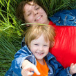 Woman and child lie on green grass — Stockfoto
