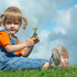 Little girl sit on green grass under sky — Stock Photo