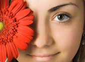 Close-up woman eyes and gerbera flower — Stock Photo