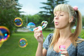 Young girl makes soap bubble — Stock Photo