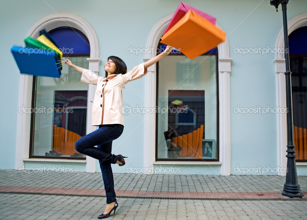 Young woman with multi-coloured bags with purchases — Stock Photo #1210598