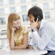 Couple sitting at table using their cell — Stock Photo