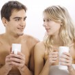 Young couple drinking on the bed — Stock Photo