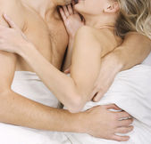 Loving affectionate nude heterosexual couple on bed. — Stock Photo