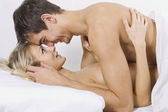 Happy couple on bed — Stockfoto