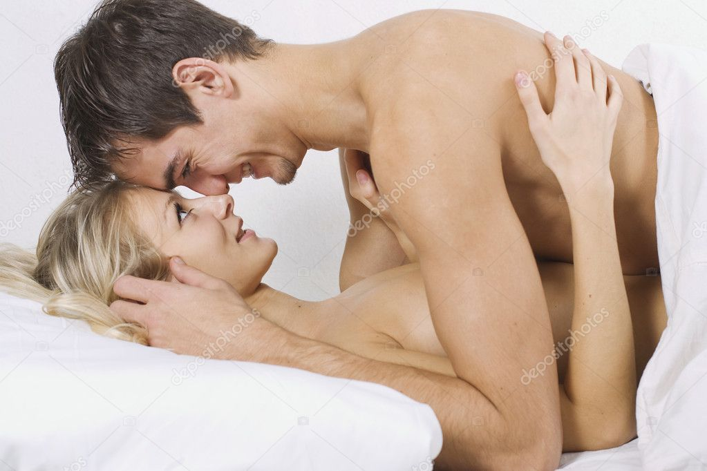Loving affectionate nude heterosexual couple on bed. — Stock Photo #1443049