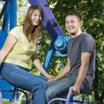 Cheerful couple on the carousel — Stock Photo