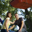 Stock Photo: Cheerful young couple on the carousel