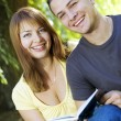 Couple reading outdoors - Stock Photo