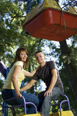 Cheerful young couple on the carousel — Stock Photo