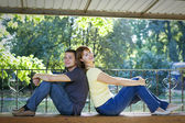 Couple sitting back to back on a bench — Stock Photo
