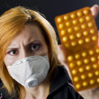 Woman wearing mask holding pills — Stock Photo