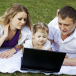 Family on picnic with laptop — Stock Photo