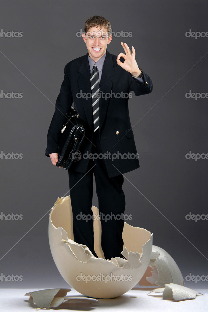 Young businessman looks out from big egg — Stock Photo #1523770