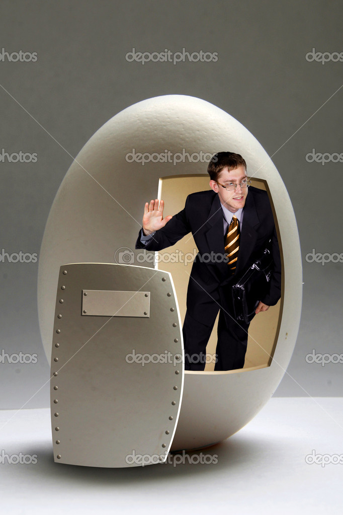Young businessman looks out from big egg  Stock Photo #1523772